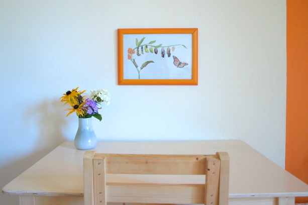 a Montessori table and chair with fresh flowers and artwork at the child's height