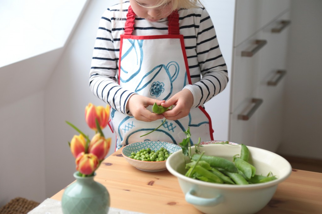 Montessori kids in the kitchen shelling peas